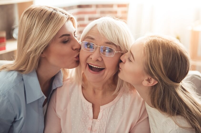 grandmother is being kissed by her daughter and granddaughter
